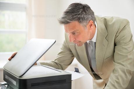 Businessman Looking At Photocopy Machineの写真素材 [FYI00640378]