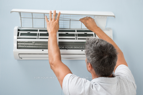 Man Cleaning Air Conditioning Systemの写真素材 [FYI00640379]