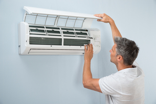 Man Cleaning Air Conditioning Systemの写真素材 [FYI00640381]