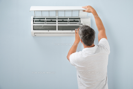 Man Cleaning Air Conditioning Systemの写真素材 [FYI00640383]