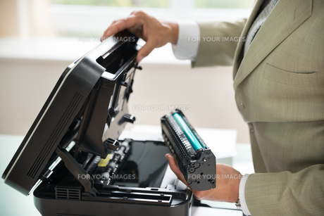 Businessman Fixing Cartridge In Photocopy Machineの写真素材 [FYI00640387]