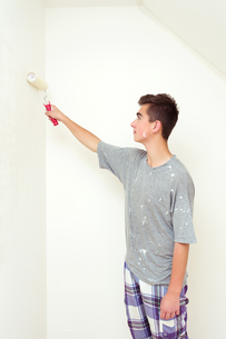 teenager painting wall to white at homeの写真素材 [FYI00640577]