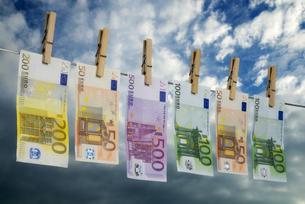 euro bills on a clothesline symbolizing money laundering.の写真素材 [FYI00641101]