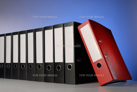 a red file folder in front of a row with black foldersの写真素材 [FYI00641103]
