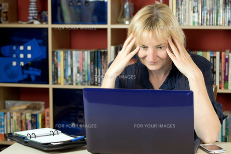 The middle aged woman is reading in the notebookの写真素材 [FYI00641406]
