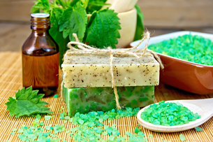 Soap homemade and oil with nettles in mortar on boardの写真素材 [FYI00641936]