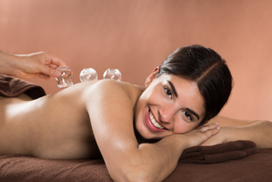 Smiling Woman Receiving Cupping Therapyの写真素材 [FYI00642138]