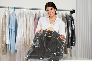 Woman Holding Suit In Shopの写真素材 [FYI00642211]