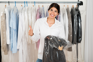 Woman Holding Suit In Shopの写真素材 [FYI00642220]