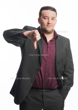 young man in suit showing thumbs downの素材 [FYI00642747]