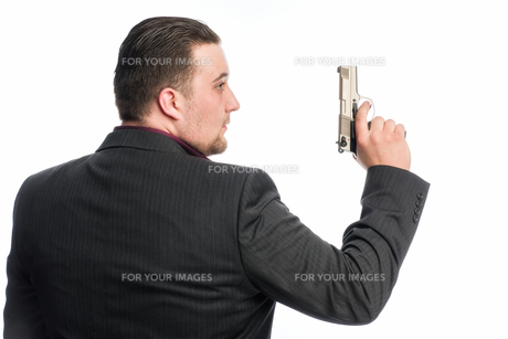 young man in suit carrying a weaponの素材 [FYI00642765]