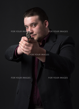 young man in suit aiming with gunの素材 [FYI00642771]