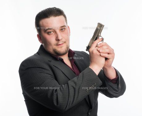 young man in suit carrying a weaponの素材 [FYI00642779]