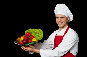 Young chef holding colander with fresh vegetablesの写真素材 [FYI00644162]