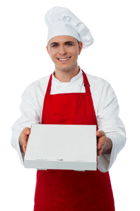 Young male chef delivering pizzaの写真素材 [FYI00644173]