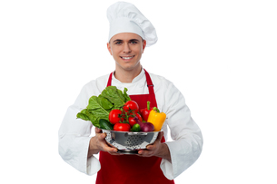 Male chef holding vegetables bowlの写真素材 [FYI00644175]