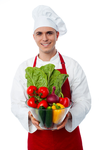 Male chef holding glass bowl full of vegetablesの写真素材 [FYI00644177]