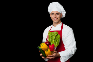 Handsome chef holding vegetables bowlの写真素材 [FYI00644181]