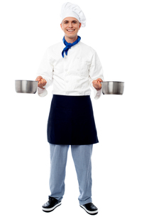 Young male chef holding empty vesselsの写真素材 [FYI00644184]