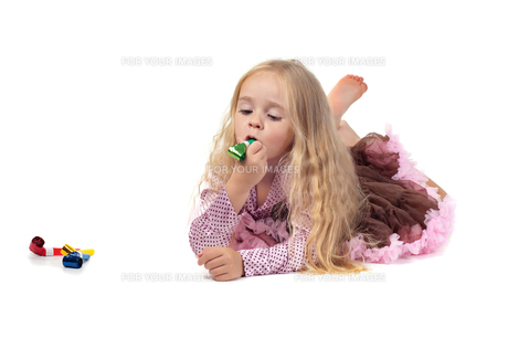 Little baby girl in tutu skirt using party blowerの写真素材 [FYI00644255]