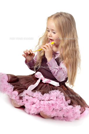 Girl in tutu skirt playing with party blowerの写真素材 [FYI00644256]