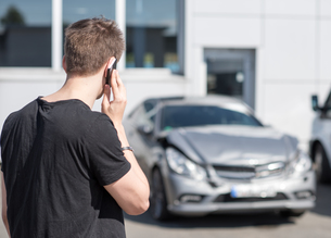 young man on the phone after a car accidentの写真素材 [FYI00644338]