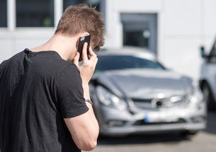 young man on the phone after a car accidentの写真素材 [FYI00644341]