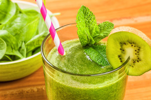 green smoothie with a slice of kiwi and mint leaves freshの写真素材 [FYI00644493]