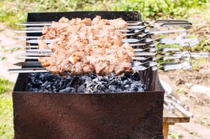 skewers with shish kebabs on brazier on backyardの写真素材 [FYI00644505]