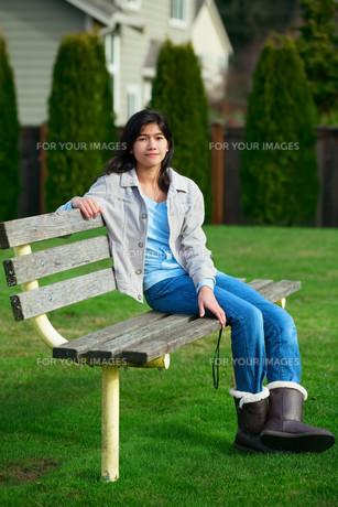 Young biracial teen girl relaxing outdoors on park benchの写真素材 [FYI00644701]