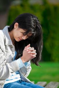 Young biracial teen girl praying outdoors on benchの写真素材 [FYI00644704]