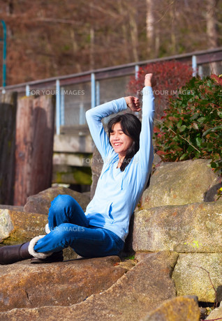 Young teen girl sitting on large boulders or rocks outdoors, arms raised over head, excited and happyの写真素材 [FYI00644724]
