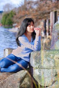 Young teen girl sitting outdoors on rocks prayingの写真素材 [FYI00644727]