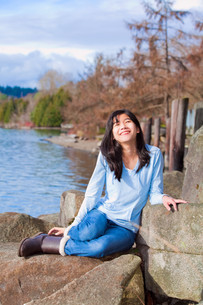 Happy young teen girl face upturned, smiling, while sitting outdoors on rocks along lake shoreの写真素材 [FYI00644728]
