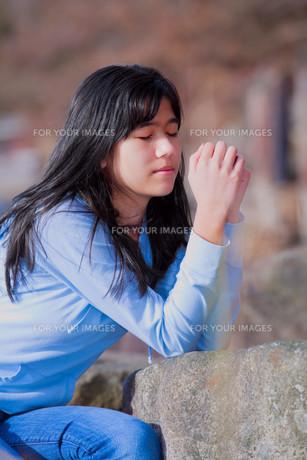 Young teen girl sitting outdoors on rocks prayingの写真素材 [FYI00644729]