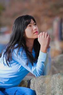 Young teen girl sitting outdoors on rocks prayingの写真素材 [FYI00644730]