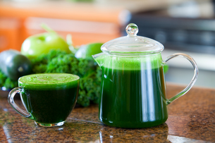 Glass cup of green vegetable juice on kitchen counterの写真素材 [FYI00644740]