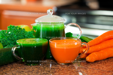 Two cups of fresh vegetable juice on kitchen counter with vegetables in backgroundの写真素材 [FYI00644741]