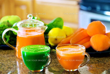Two cups of fresh vegetable juice on kitchen counter with vegetables in backgroundの写真素材 [FYI00644744]