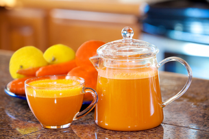 One cup of orange colored juice on kitchen counter with fruit and vegetables in backgroundの写真素材 [FYI00644745]