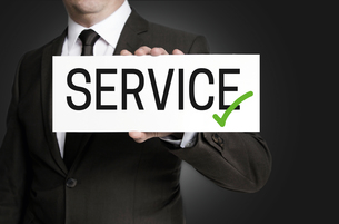 service shield is held by businessmanの写真素材 [FYI00645039]