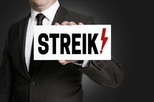 strike shield is held by businessmanの写真素材 [FYI00645041]