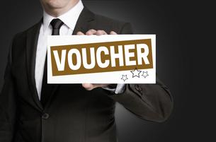 voucher shield is held by businessmanの写真素材 [FYI00645049]