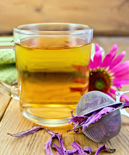 Tea from Echinacea in glass mug with strainer on boardの写真素材 [FYI00645432]