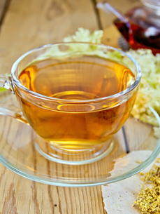 Tea from meadowsweet in cup and teapot on boardの写真素材 [FYI00645454]