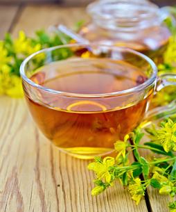 Tea from tutsan in glass cup and teapot on boardの写真素材 [FYI00645457]