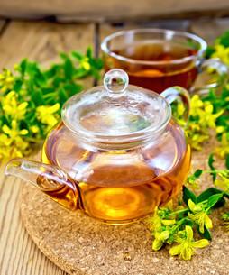 Tea from tutsan in glass teapot and cup on boardの写真素材 [FYI00645462]