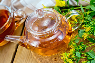 Herbal tea from tutsan in glass teapot with cup on boardの素材 [FYI00645463]