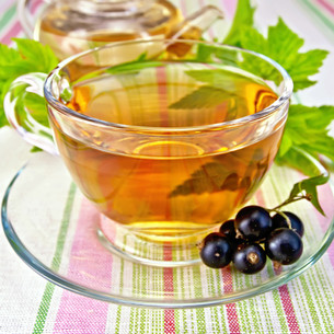 Tea with blackcurrants in cup on tableclothの写真素材 [FYI00645483]