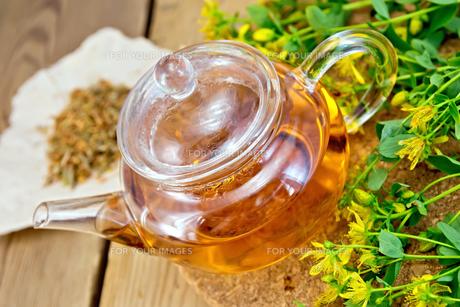 Tea with fresh and dry tutsan in glass teapo on boardの素材 [FYI00645486]